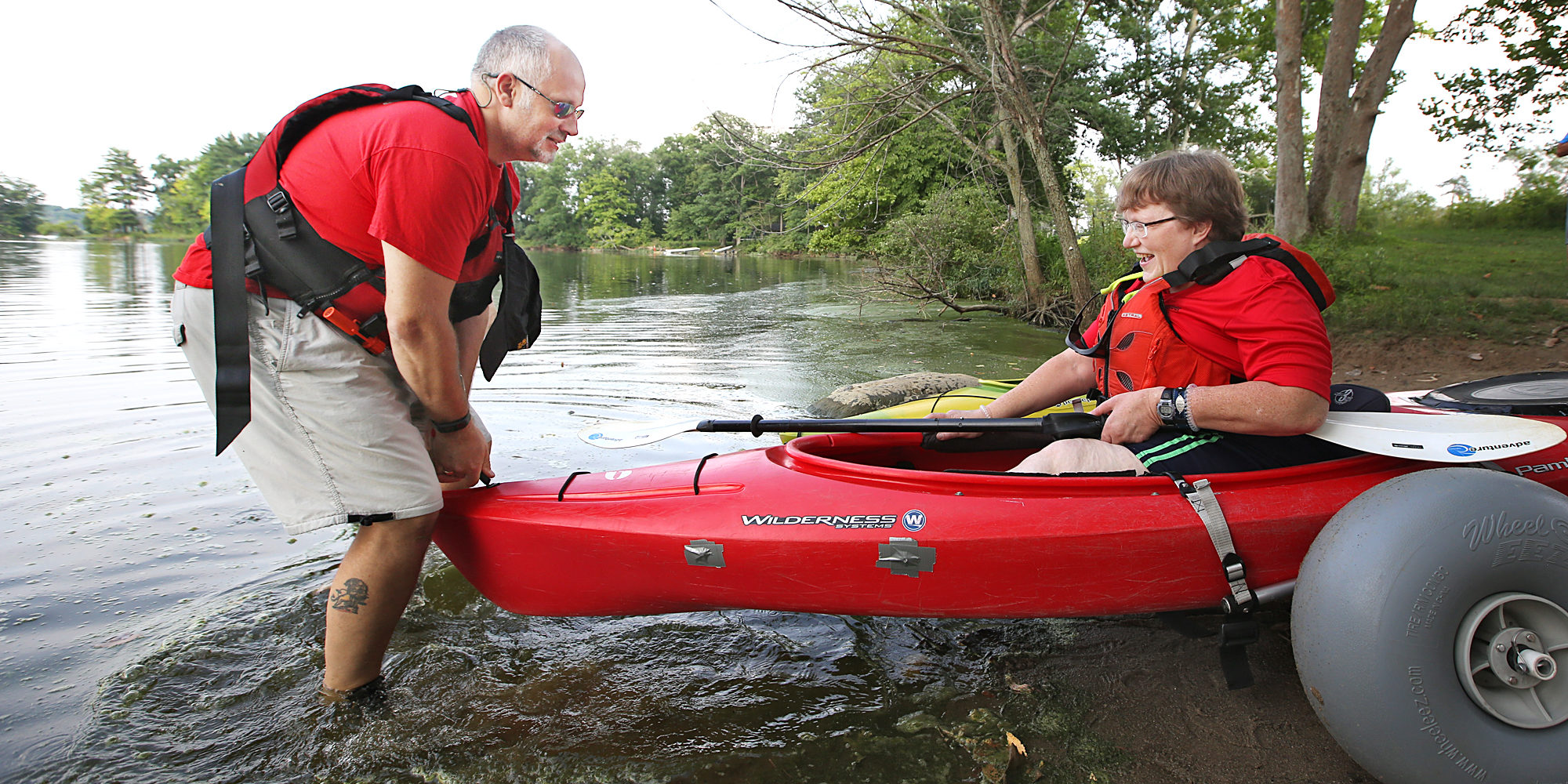 A TAASC (The Adaptive Adventure Sports Coalition) volunteer helps Laura Krietemeyer out onto the water for  an evening kayaking adventure on the Scioto River on July 28, 2015.  Laura is disabled and volunteers for TAASC. (Chris Russell/Dispatch Photo)